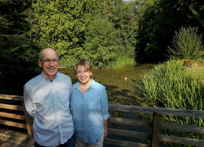 Tom and Marnie Malpass pose for a portrait next to the pond at their Bainbridge Island home in September.