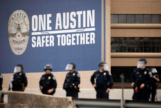 Austin police officers gathered on Interstate 35 to remove protesters demonstrating against police brutality from the highway in May. Gov. Greg Abbott and other state leaders have criticized Austin officials' decision to cut police department funding.