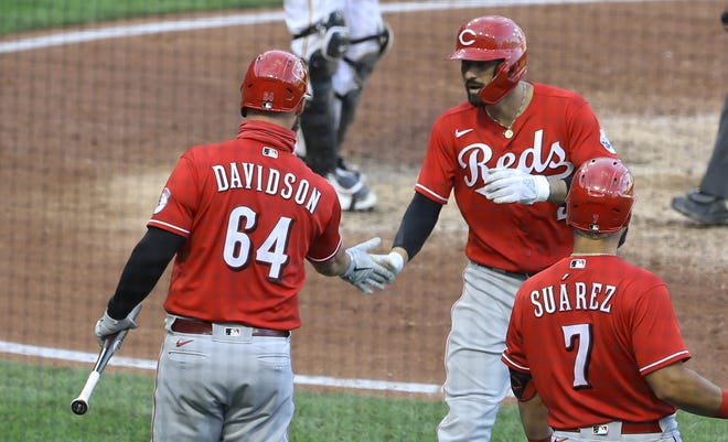 Sep 4, 2020; Pittsburgh, Pennsylvania, USA;  Cincinnati Reds designated hitter Matt Davidson (64) congratulates right fielder Nick Castellanos (middle) on his solo home run against the Pittsburgh Pirates during the fifth inning at PNC Park. Mandatory Credit: Charles LeClaire-USA TODAY Sports