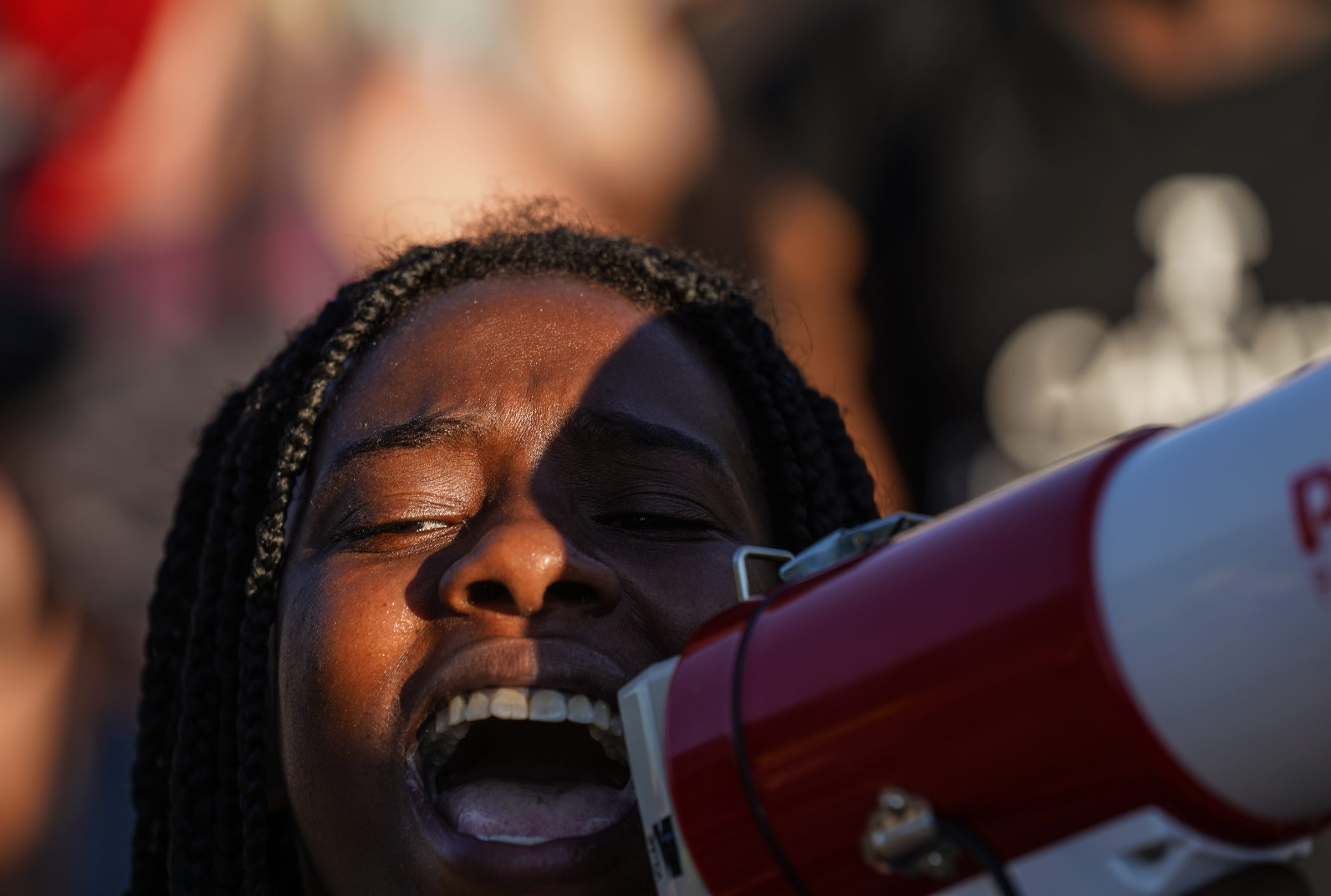 Shaqualla Johnson of Detroit shouts a chant while marching with other protesters in Southwest Detroit neighborhood on Monday, June 29, 2020.