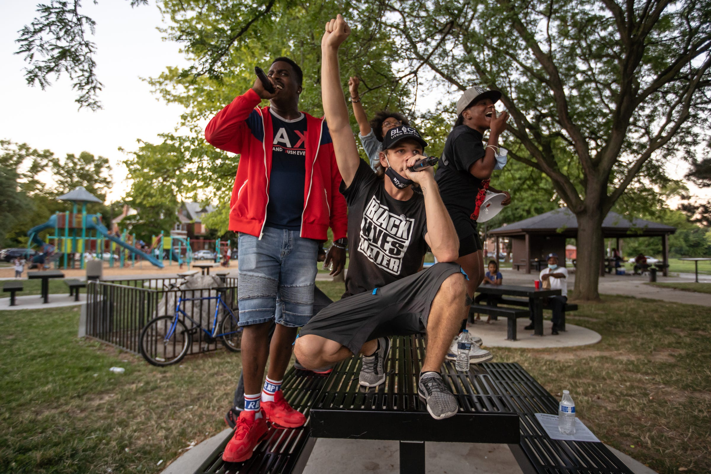 Brendan Scorpio (foreground) of Detroit raises his fist while returning to Bennett Playground with other Detroit Will Breathe members (left to right) Jae Bass of Detroit, Sammie Lewis of Detroit and Shaqualla Johnson of Detroit after marching against police brutality through Detroit's north side on Tuesday, August 18, 2020.