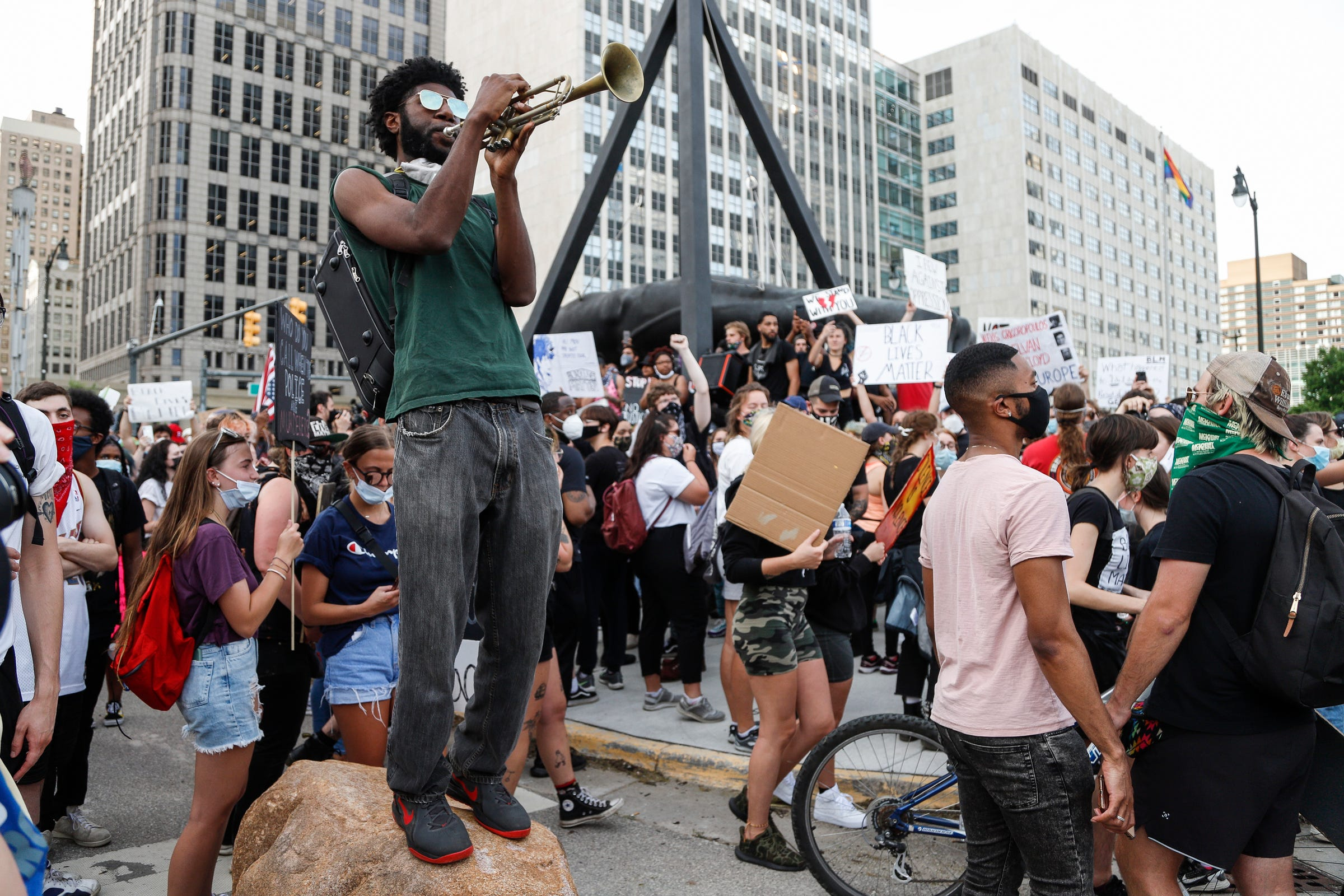 Allen Dennard of Detroit plays trumpet as the crowd gather around the Monument to Joe Louis or The Fist, as it is commonly known, in downtown Detroit, Wednesday, June 3, 2020.