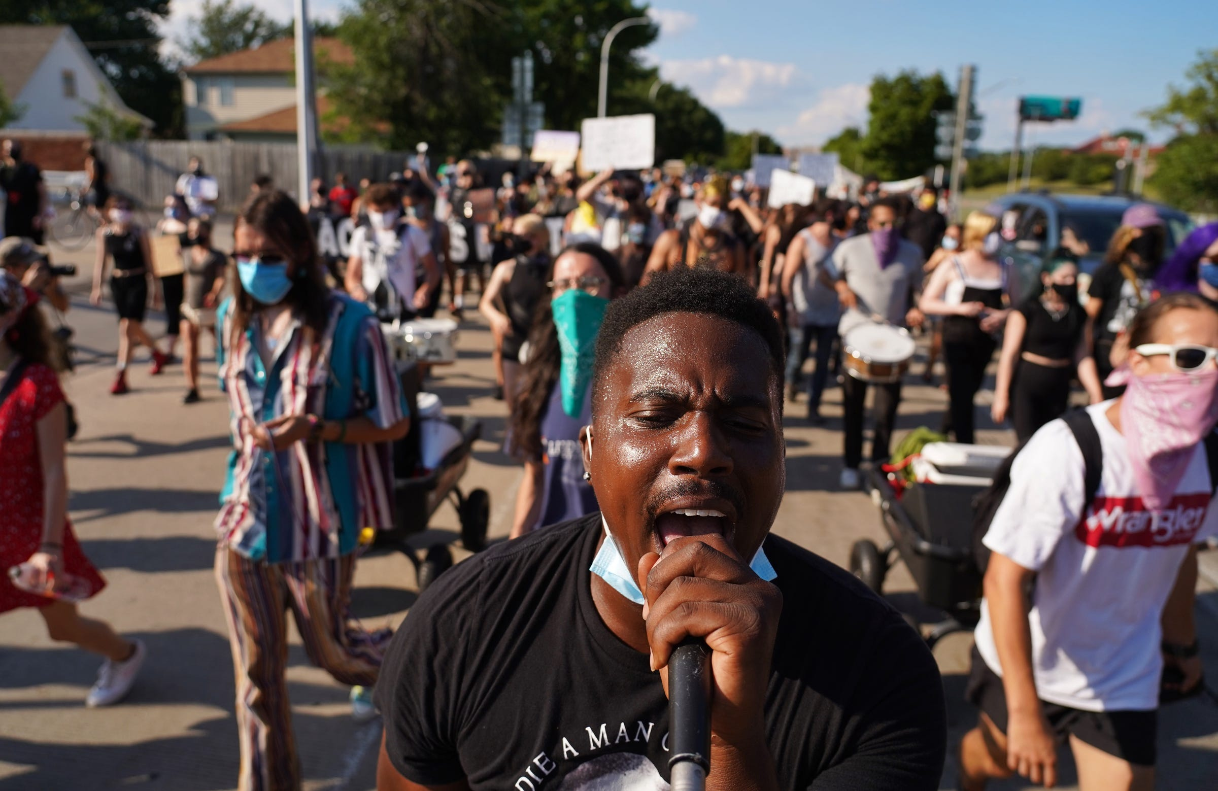 Jae Bass of Detroit leads protesters in a chant while marching against police brutality through Harper Woods on Friday, July 24, 2020.