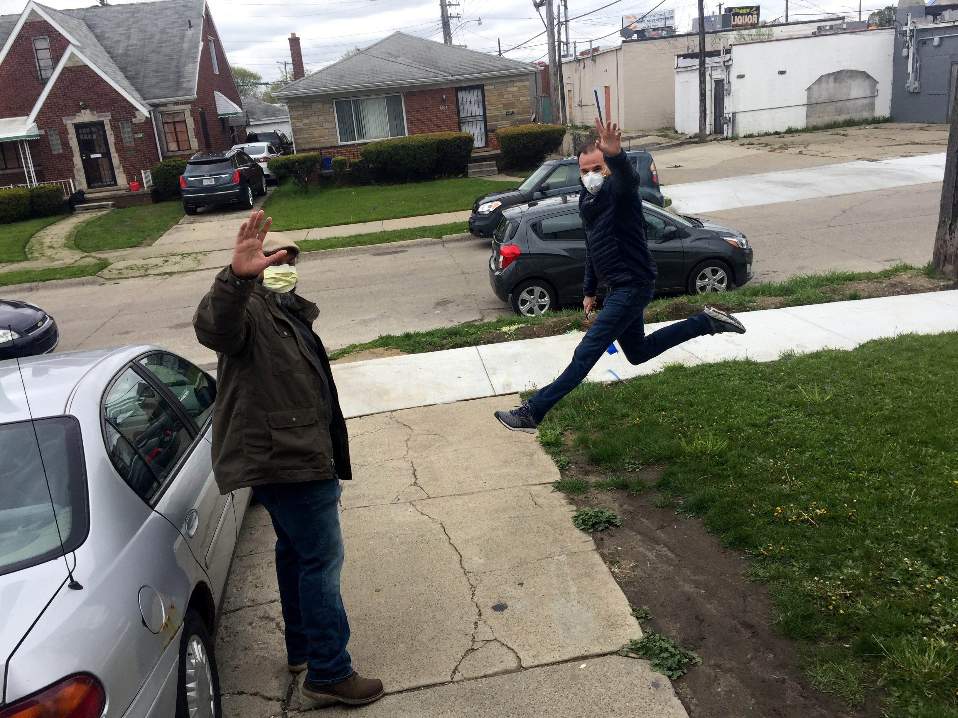 Capturing Belief co-founders Khary Mason, left, and Romain Blanquart, right,  wave goodbye to Dejuan McCurrie, 13, after visiting him at home on Detroit's east side on May 11, 2020. Dejuan has been attending Capturing Belief for a couple years but since the COVID-19 pandemic started and in-person classes stopped he does not have access to a camera so his mentors dropped of one off for him to use during remote photography classes.