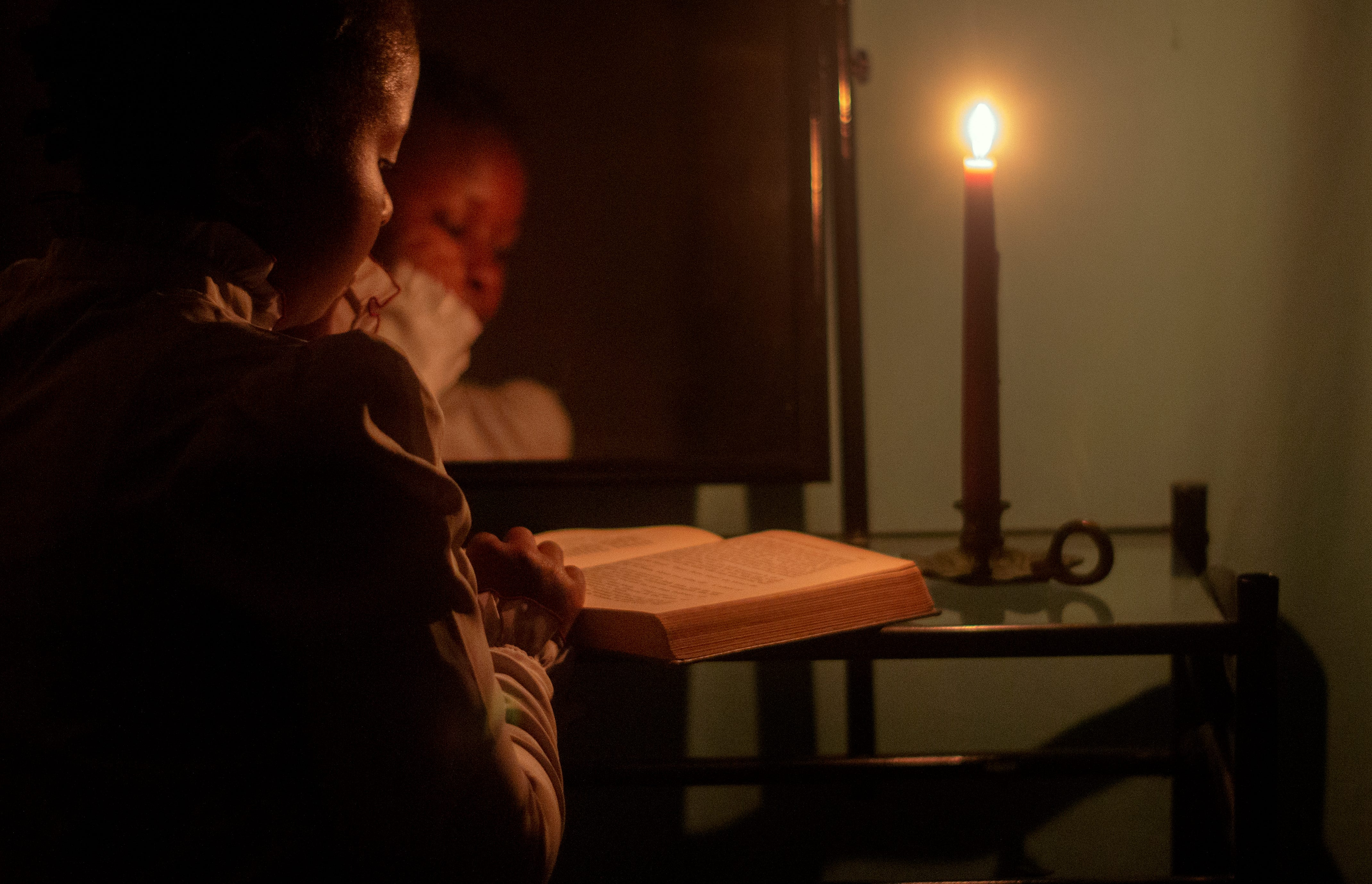 In this self portrait of myself reading Moby Dick by candlelight at my vanity in my bedroom, at home in Detroit on August 31, 2020. I made this image to capture a moment of stillness, serenity and contentment during a time when everything feels unstable and many continue to feel a sense of foreboding.