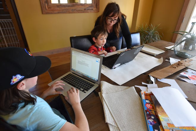 Emily Love helps her 7-year-old son Foster, a first grader at Pioneer Elementary School in Lafayette, with his work on March 31, 2020, the first day all students in the Boulder Valley School District migrated to online learning during the coronavirus shut down. His older brother, Miles, 12, is working in a Google chat room on a physical science problem with one of his 6th grade classmates from Manhattan Middle School in Boulder.