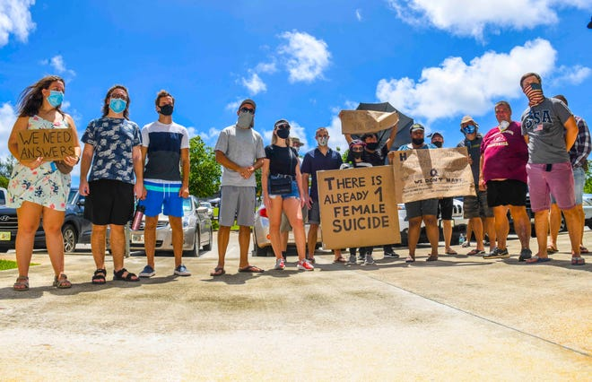 A group of Russian nationals gather in front of a building that houses immigration services offices in Tamuning, during a protest on Friday. The group was trying to raise awareness problems relating to asylum after fleeing Russia. Egor Elkin, originally from Izhevsk, the capital city of Udmurtia, Russia, said members of the group have been hampered in scheduling immigration hearings.