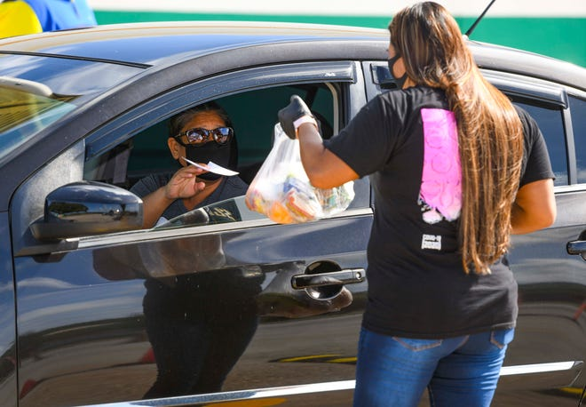 John F. Kennedy High School school aide Sara Siguenza presents a bundle of non-perishable breakfast foods to a driver during a Guam Department of Education school meal distribution in this Sept. 4 file photo.