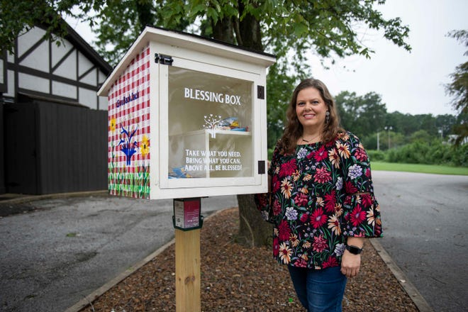 Allison Shipp stocks a Blessing Box with snacks and hygiene items in Jackson, Tenn., Friday, Sept. 4, 2020.
