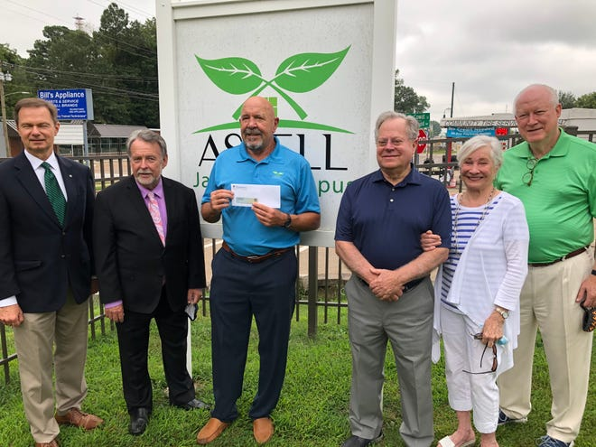 Aspell Recovery Director Richard Barber, center, accepts a check for an undisclosed amount from the West Tennessee Healthcare Foundation and the Kirkland family while flanked by Frank McMeen, Steve Bowers, Carl Kirkland, Alice Kirkland and Ron Kirkland.