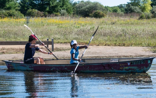 Tom and Nyya Manion of Columbus, Ohio launch a canoe into Lake Ovid Friday, Sept. 4, 2020, at Sleepy Hollow State Park in Laingsburg, where they are camping for Labor Day weekend.   Park attendance has surged during the coronavirus pandemic.