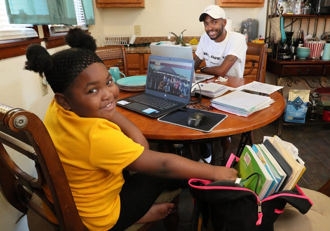 Harmonee Griffin, 6, is in first grade at King's Academy.   She does her virtual learning on the kitchen table, where she and her father, Brooks Griffin, right, have established a home office.  On this early September day she was doing schoolwork but not online at the moment.