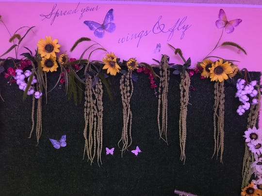 "A ""grass wall"" in Neke Marche's beauty supply store and wig bar features flowers that reference her family's history."