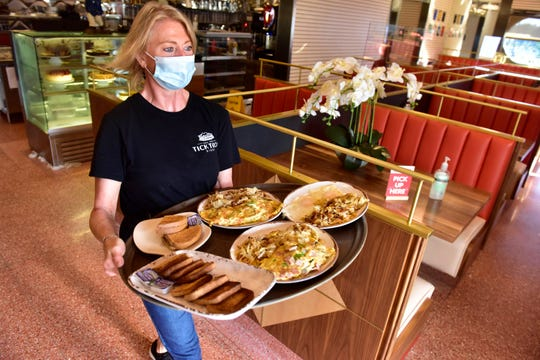 Lisa Fenner, a server, brings food out of the kitchen on the first day of indoor dining at the Tick Tock Diner in Clifton, N.J. on Friday Sept. 4, 2020. Indoor dining was banned on March 16, 2020 due to the coronavirus pandemic.
