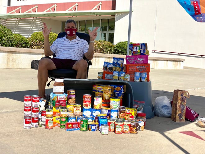 New Mexico State director of athletics Mario Moccia poses with the donations from his drive-by food drive on Thursday at the Fulton Center.