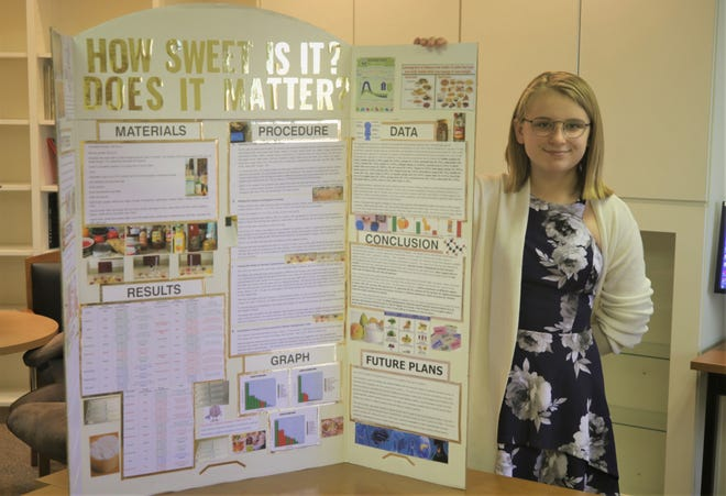 Tibbetts Middle School eighth-grader Alex Bessinger displays the science project that helped her become a semifinalist in a national STEM competition.