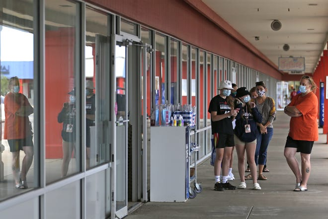 Shoppers wait in line Wednesday, Aug. 5, 2020, at The Outlet Shoppes at Oshkosh on South Washburn Street.