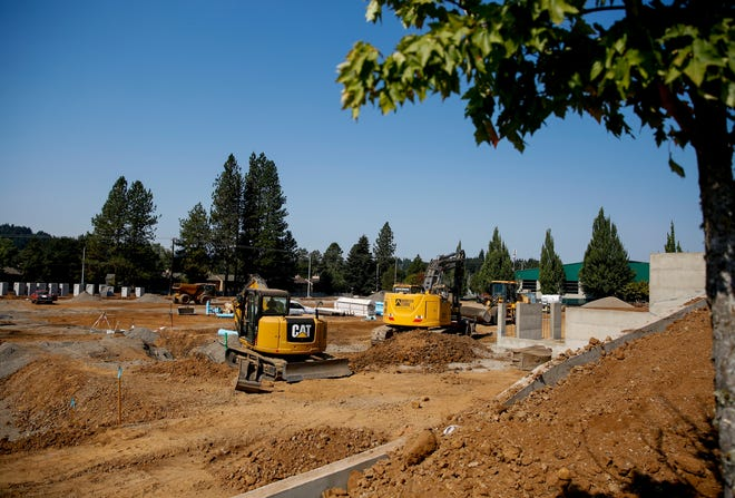 Construction workers develop land on Friday, Sept. 4, 2020 at the intersection of Commercial Street and Robins Lane in Salem, Ore.