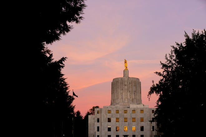 The sunset is reflected in the windows of the Oregon State Capitol in Salem, Oregon on Tuesday, Sept. 1, 2020.