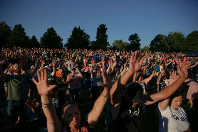 People raise their hands in worship during the Let Us Worship event on Thursday, Sept. 3, 2020 at Riverfront Park in Salem, Ore.