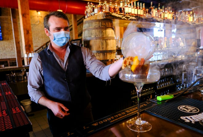 Smoke swirls as manager Charlie Dominick unveils a freshly made Smoking Gun Maple Old Fashioned Thursday, Sept. 3, 2020, at Brick & Bourbon in St. Cloud.