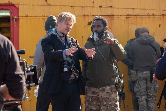 "Director Christopher Nolan (left) goes over a scene with John David Washington on the set of ""Tenet."""