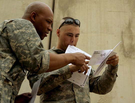 U.S. Army Cpl. Sean Morton, 25, of Boston consults with a colleague before mailing his absentee ballot for the presidential election at Forward Operating Base Marez in Mosul, Iraq, on Oct. 22, 2008.