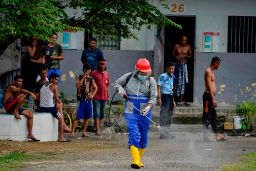 An inmate (L) sprays disinfectant as part of measures against the COVID-19 coronavirus at a prison in Banda Aceh on September 3, 2020.