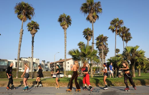 People roller skate along Venice Beach amid the COVID-19 pandemic on September 3, 2020 in Venice, California. Retailers are reporting high demand for roller skates as people search for outdoor activities amid lifestyle restrictions due to the coronavirus. According to Google data, roller skating related searches from March to May nearly quadrupled.
