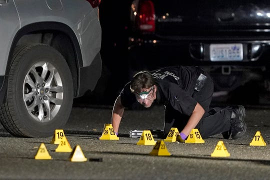 A Washington State Patrol Crime Lab worker looks at evidence markers in the early morning hours of Friday, Sept. 4, 2020, in Lacey, Wash.
