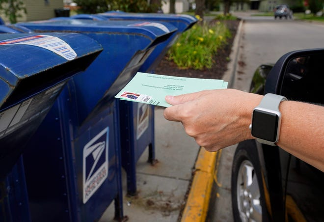 Dropping application for mail-in ballot into a mail box.
