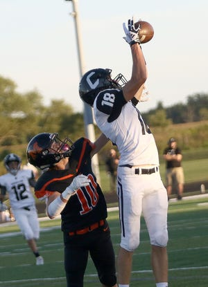 Carrollton's Talen Timberlake (18) pulls down a first-quarter touchdown pass defended by Marlington's Luke Tortola during conference action at Marlington High School Friday, September 4, 2020.