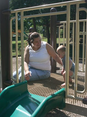 Josette Miller plays with her nephew, Brock, 1 year old, at the Tot Lot at Brookside Park on Saturday on a warm, sunny day.