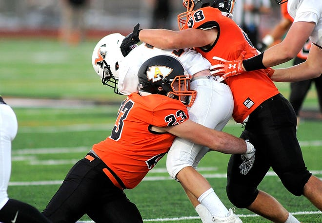 Ashland High's Jakob Beverly (23) and Sean Hanna (58) tackle Mount Vernon's AJ Keen (34) during high school football action Friday at Community Stadium.