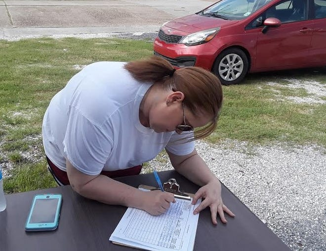 Dolly Sevin signs a petition Saturday calling for the recall of Gov. John Bel Edwards.