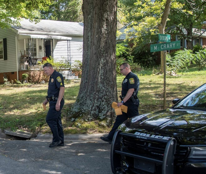 Two police officers leave the scene after shots were fired into a home on Dixon Street near McCrary Street.