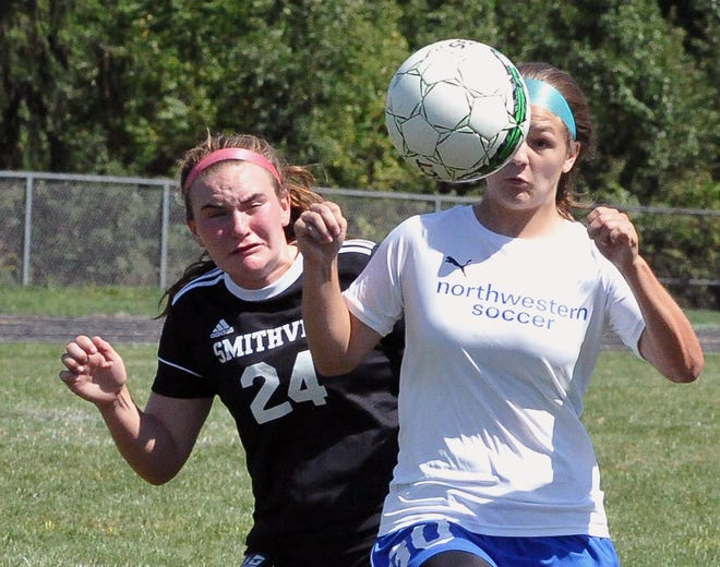 Northwestern Emma Nicholson eyes this ball as Smithville Hailey Thorn is blocked out.