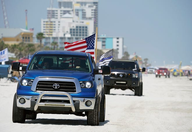 Trucks cruise the beach in Daytona Beach on Saturday as the sands were filled with participants of the Daytona Truck Meet and other visitors here for Labor Day weekend.