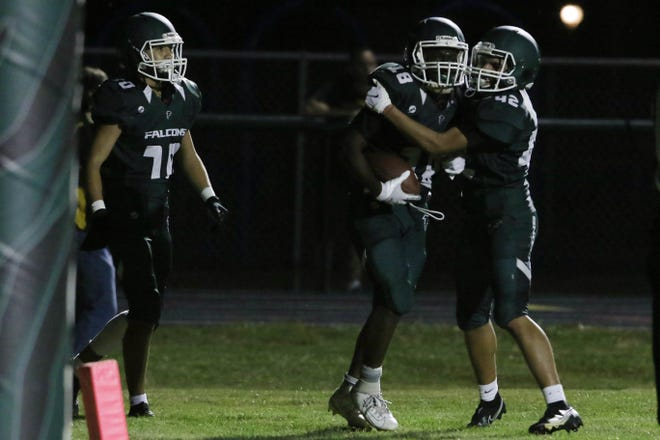West Burlington-Notre Dame's Travain Donaldson (18) celebrates with teammate Kobe Twillie (42) after scoring during the first half of their game against Fairfield High School, Friday, Sept. 4, 2020, at West Burlington's Bill Nelson Field.