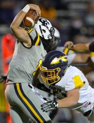 Cuyahoga Falls quarterback Tyler Harris, left, is sacked by Copley defensive end Nick Ezzie during the Black Tigers' 40-6 loss to Copley at Clifford Stadium Sept. 4.