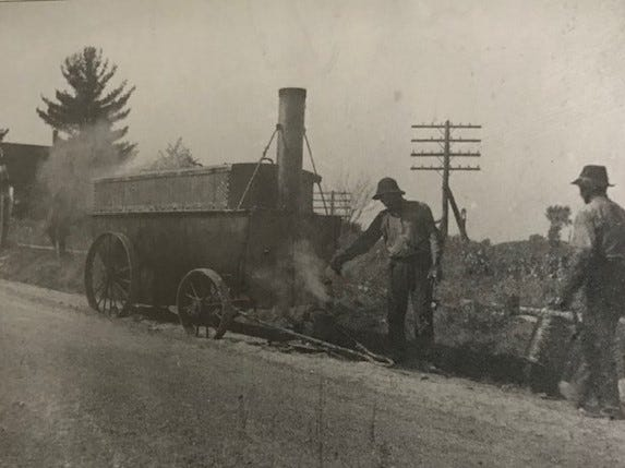 Men working on the first road paving on East Garfield near the railroad depot.