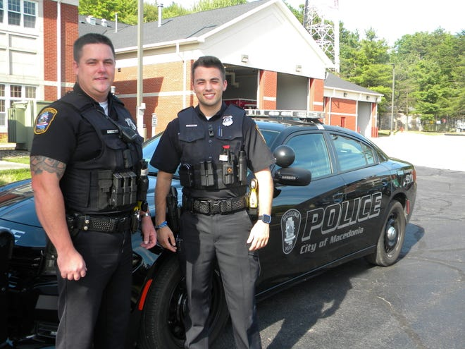Macedonia patrolmen Terry Schneider, left, and Matt Newrones stand beside one of the city's cruisers. The department along with the Northfield Village Police Department recently upgraded their certification in state policing standards. They are two of only three law enforcement agencies in Summit County to boast of the achievement.