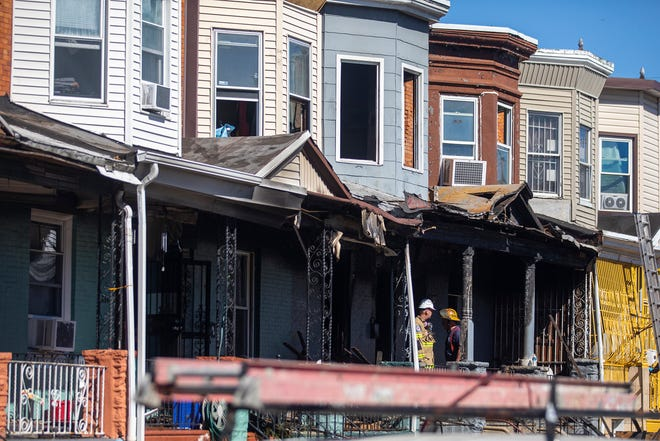 Firefighters investigate the scene after a row home fire in Philadelphia on Saturday. Fire Commissioner Adam Thiel said fire crews were called to the blaze in the Kensington neighborhood shortly before 8 a.m. Saturday and found heavy flames and smoke in the first and second floors.
