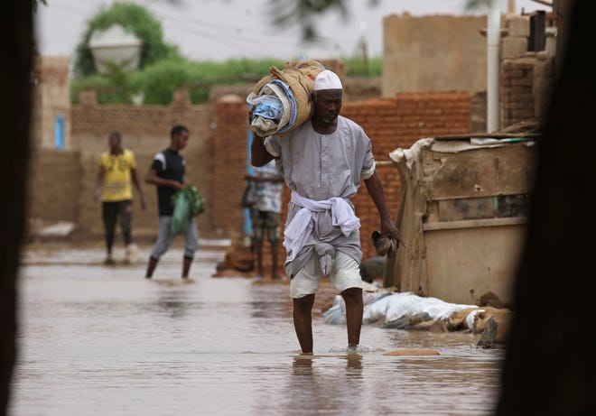 A man carries belongings as he wades through of a flooded road in the town of Shaqilab, about southwest of the capital, Khartoum, Sudan, on Monday.