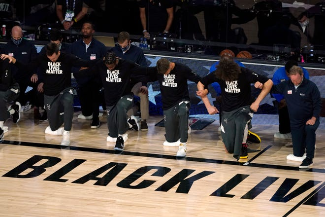 In this Aug. 29 photo, members of the Milwaukee Bucks join arms as they kneel during the national anthem before an NBA first-round playoff game against the Orlando Magic in Lake Buena Vista.