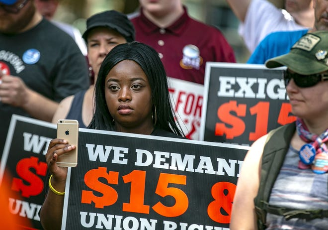 Protesters listen to speeches as the Alachua County Labor Coalition and Free College Now tour joined to protest the treatment of OPS workers at the University of Florida and for a $15 an hour minimum wage in front of University of Florida President W. Kent Fuchs' house in July 2018.