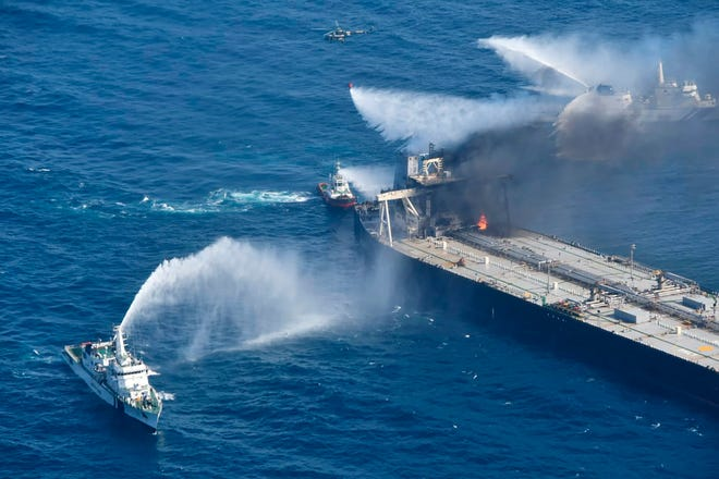 Tug boats and ships battle the fire on MT New Diamond, off the eastern coast of Sri Lanka in the Indian Ocean on Saturday. The fire on the large oil tanker off Sri Lanka's coast has been brought under control but is still not extinguished, the navy said Saturday. The tanker, carrying nearly 2 million barrels of crude oil, was drifting about 20 nautical miles from Sri Lanka's eastern coast and on Friday evening a tug boat towed it to the deep sea away from land, said navy spokesman Capt. Indika de Silva.