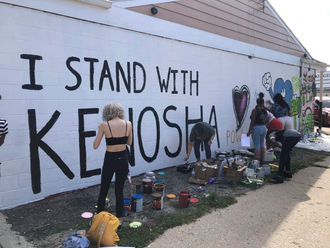"""Volunteers paint murals on boarded-up businesses in Kenosha, Wis., on Aug. 30 at an """"Uptown Revival."""" The event was meant to gather donations for Kenosha residents and help businesses hurt by violent protests that sparked fires across the city following the police shooting of Jacob Blake."""