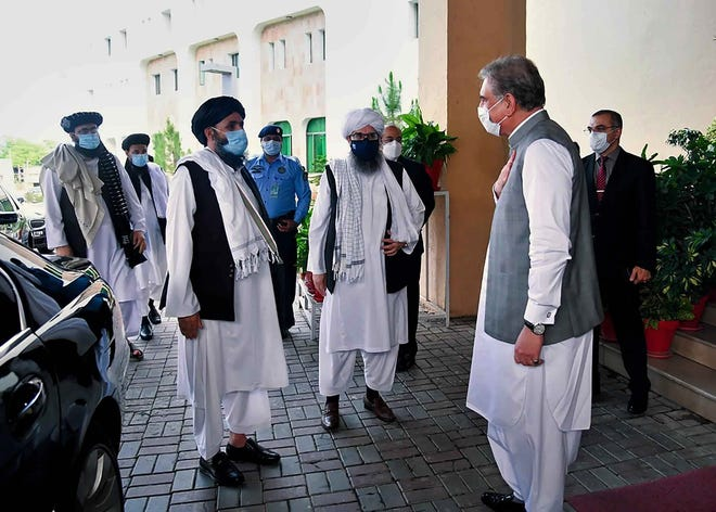 Foreign Minister Shah Mahmood Qureshi, right, greets members of a Taliban political team on their arrival at the Foreign Ministry for talks, in Islamabad, Pakistan, last month.