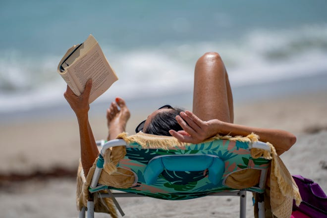 A beachgoer basks in the sun while reading a book on Midtown Beach in Palm Beach Friday. The town said it is closing the beaches during Labor Day weekend to combat the spread of the coronavirus. [GREG LOVETT/palmbeachpost.com]